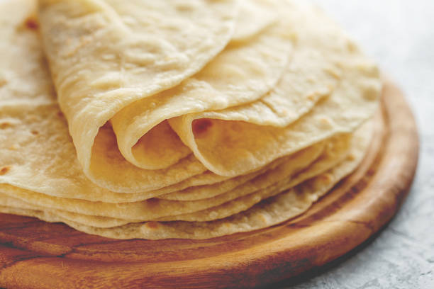 stack of homemade wheat flour tortilla wraps on wooden cutting board. - tortilla stock photos and pictures