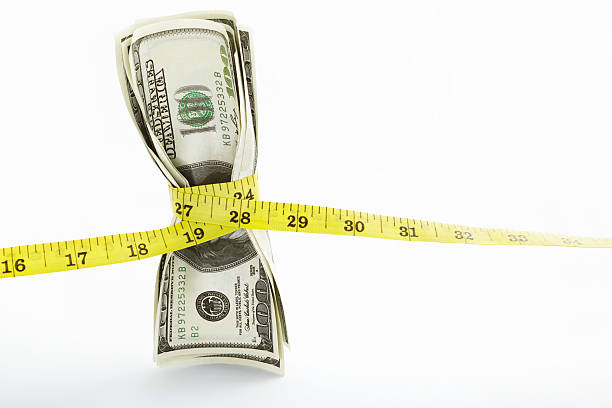 Stack of hundred dollar bills with a tape Measuring tape twining several US$100 bills over white background tighten stock pictures, royalty-free photos & images