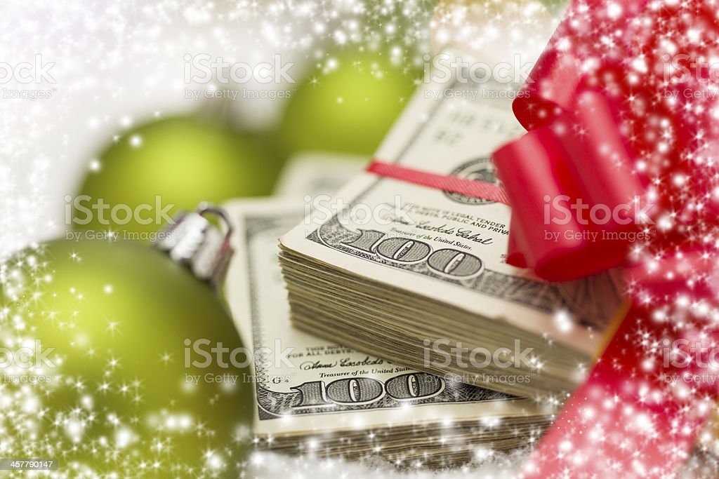 A stack of hundred dollar notes with Christmas decorations stock photo