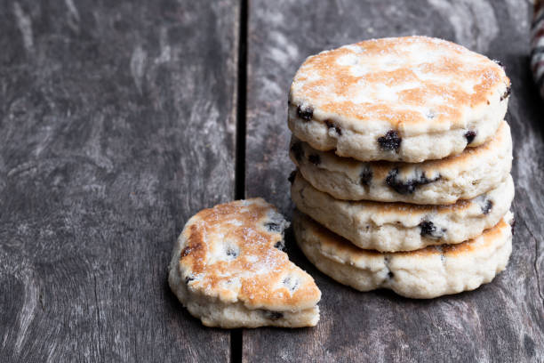 Stack of iced Welsh cakes on rustic wooden table Stack  of iced Welsh cakes on rustic wooden table welsh culture stock pictures, royalty-free photos & images