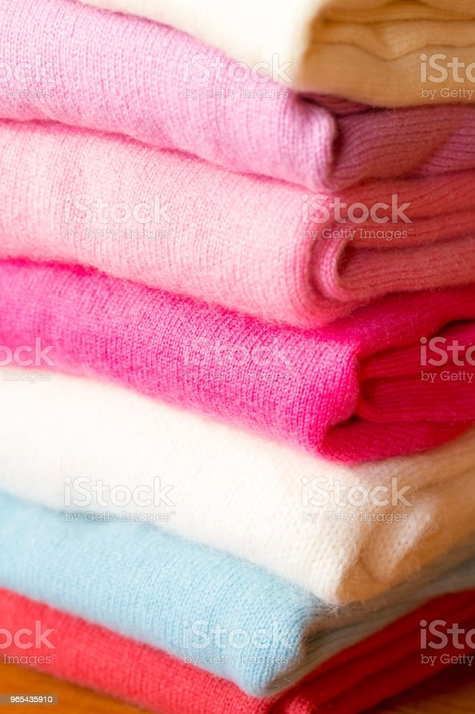 A stack of knitted sweaters of different colors lies. royalty-free stock photo