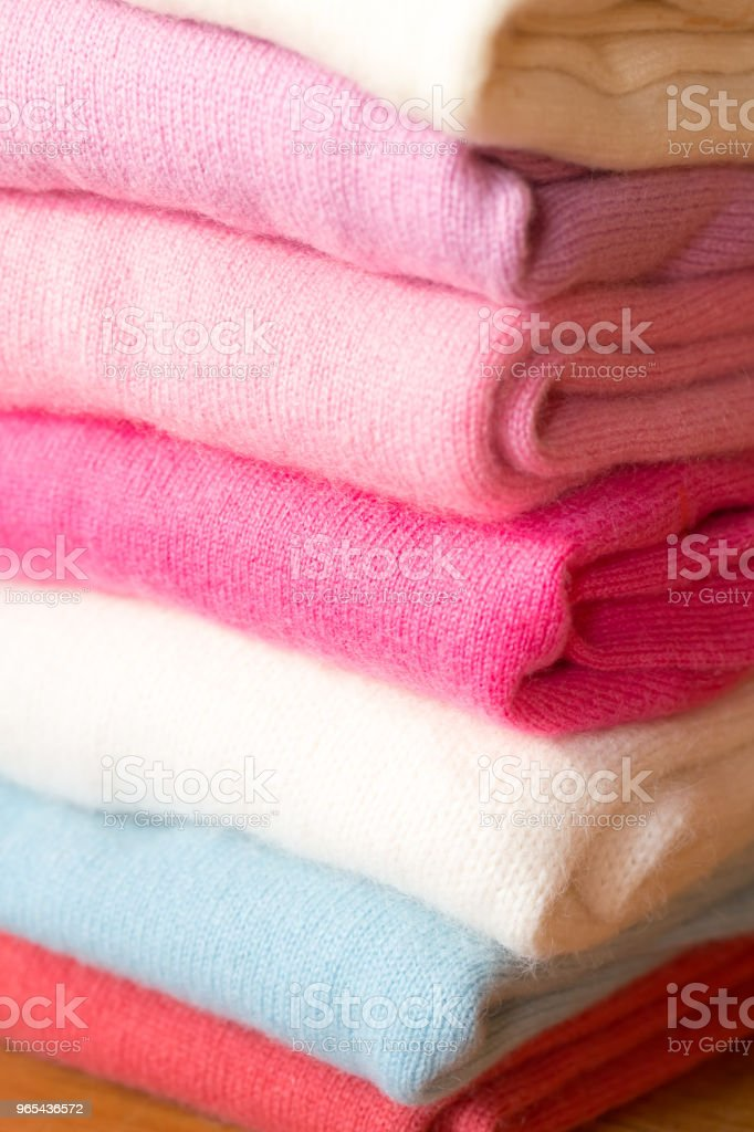 A stack of knitted sweaters of different colors lies. zbiór zdjęć royalty-free