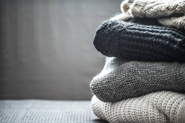 a stack of knitted sweaters - caxemira imagens e fotografias de stock
