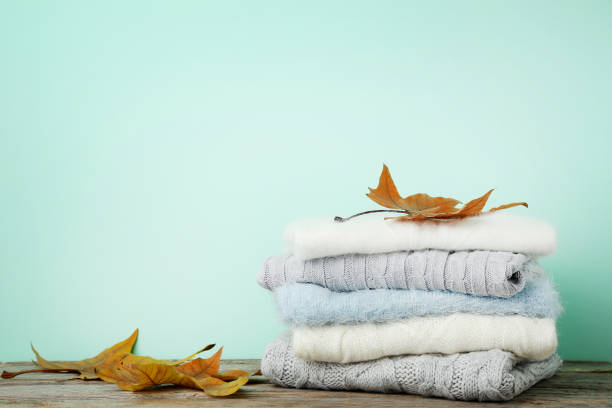 stack of knitted sweaters with autumn leafs on mint background - caxemira imagens e fotografias de stock