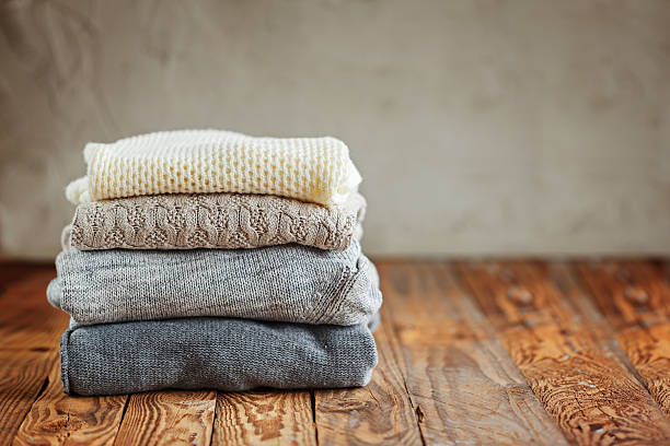 Stack of knitted winter clothes on wooden background, sweaters, space stock photo
