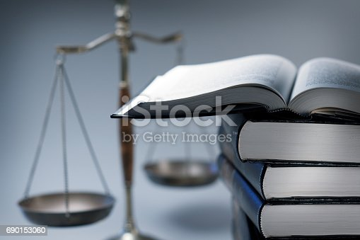 A stack of law books stands in front of a justice scale that is slightly out of focus.  On top of the stack is an open law book.