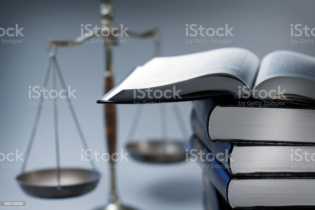Stack Of Law Books In Front Of Scales Of Justice stock photo