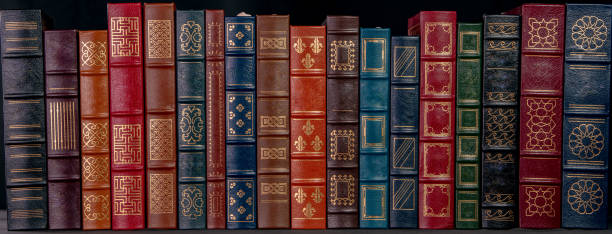 A stack of leather bound books with gold decoration stock photo