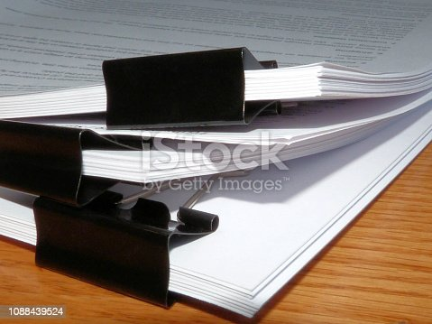 A stack of paper documents of a legal office on a wood grain desk surface with large black binder clips.