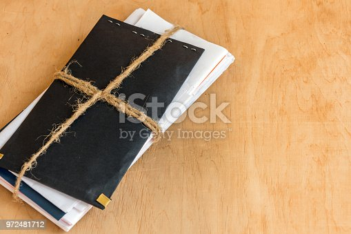 968272356istockphoto Stack of letters tied with rope on the wooden table background. 972481712