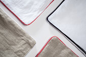 Stack of linen bedding on grey background.