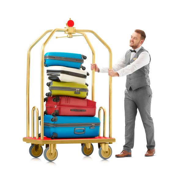 pila de equipaje empujada por trabajador de hotel - foto de stock