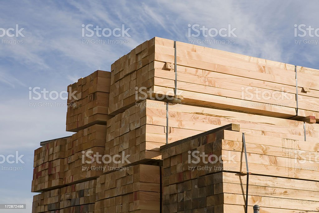 Stack of lumber in lumberyard or construction site royalty-free stock photo