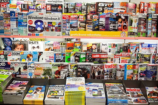 Stack of magazines Amsterdam, the Netherlands - July 2, 2013: Stack of popular magazines on the outside of the street side newsstand. Auto, computer, footballl and photography magazines can be seen. magazine rack stock pictures, royalty-free photos & images