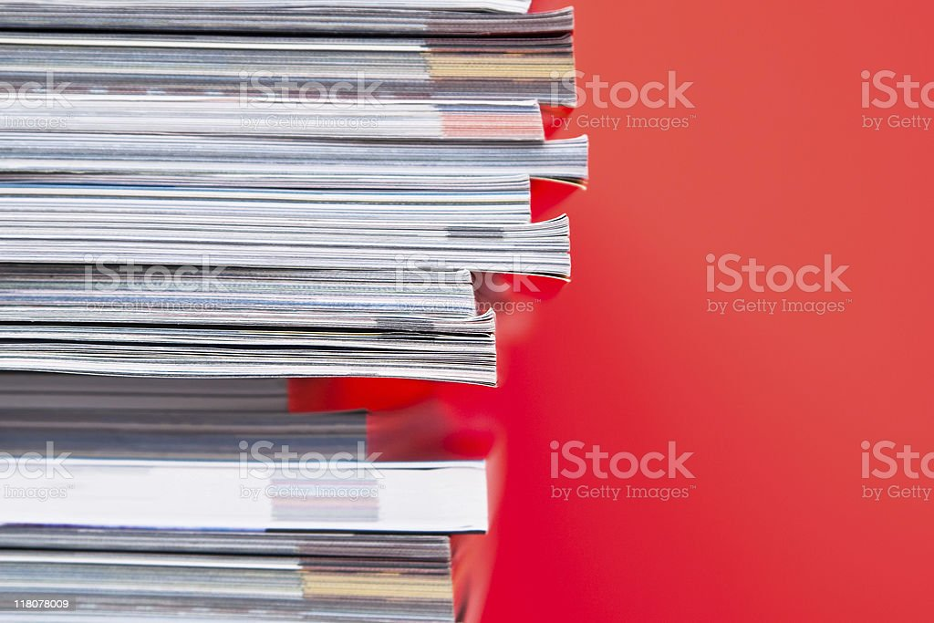 Stack of magazines set in front of red wall stock photo