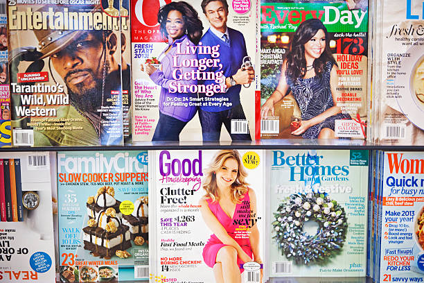 """Stack of magazines # 10 XL """"New York City, USA - December 17, 2012: Stack of popular magazines on the outside of the street side newsstand on Broadway Upper West. Entertainment, The Oprah Magazine, Every Day, Good Housekeeping and Beter Homes and Gardens can be seen."""" magazine rack stock pictures, royalty-free photos & images"""
