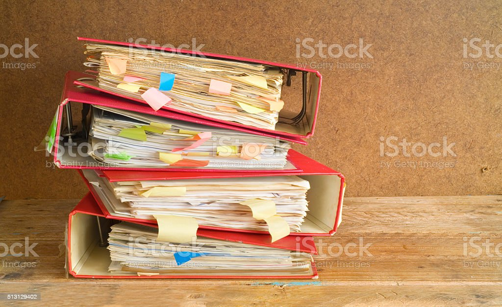 stack of messy file folders and documents, stock photo