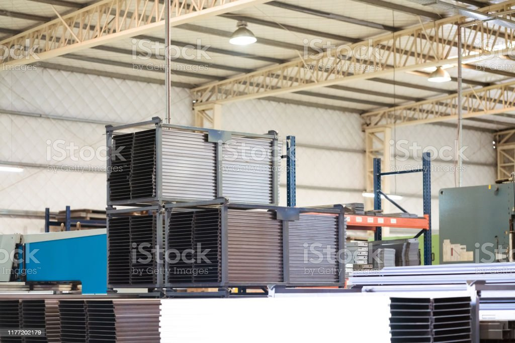 Stack of metallic sheets on rack in industry Stack of metallic sheets on rack. Low angle view of arranged machine parts. These are in manufacturing industry. Absence Stock Photo