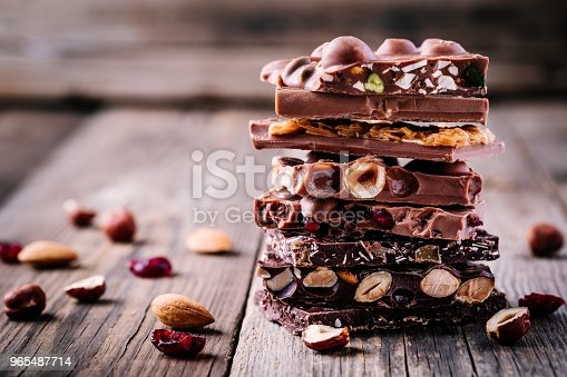 Stack of milk and dark chocolate with nuts, caramel and fruits and berries on wooden rustic background.