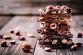 Stack of  milk and dark chocolate with nuts, caramel and fruits and berries on wooden background.