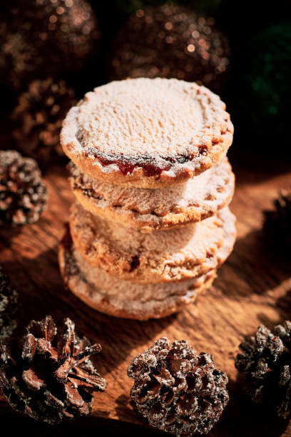 Stack of Mince Pies against a dark rustic wood surface with pine cones Christmas decorations. stock photo