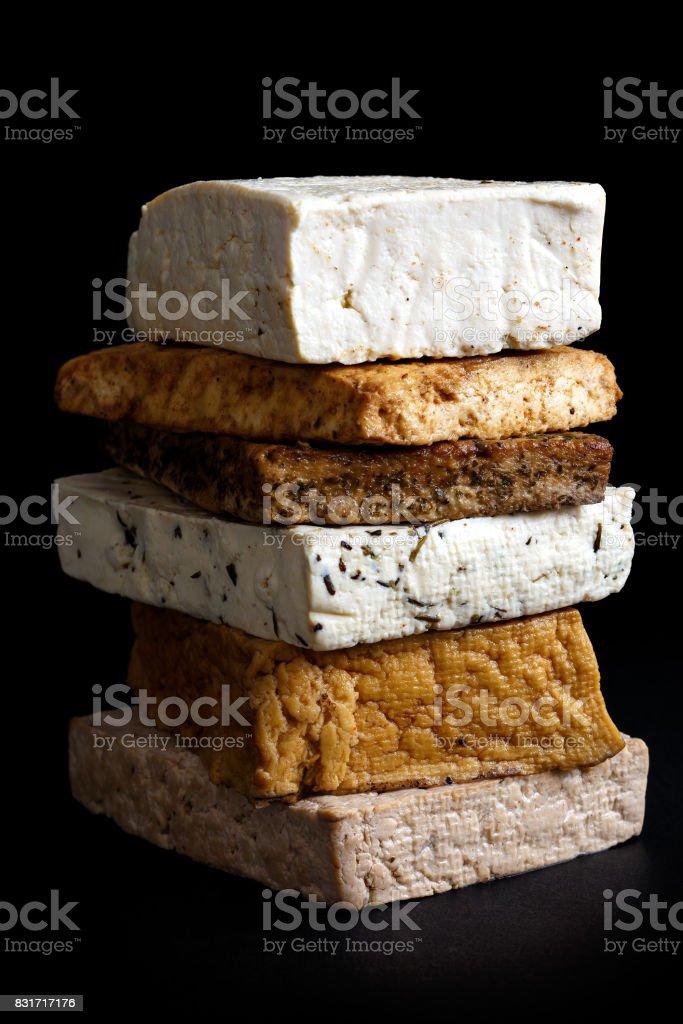 Stack of mixed tofu blocks isolated on black. stock photo