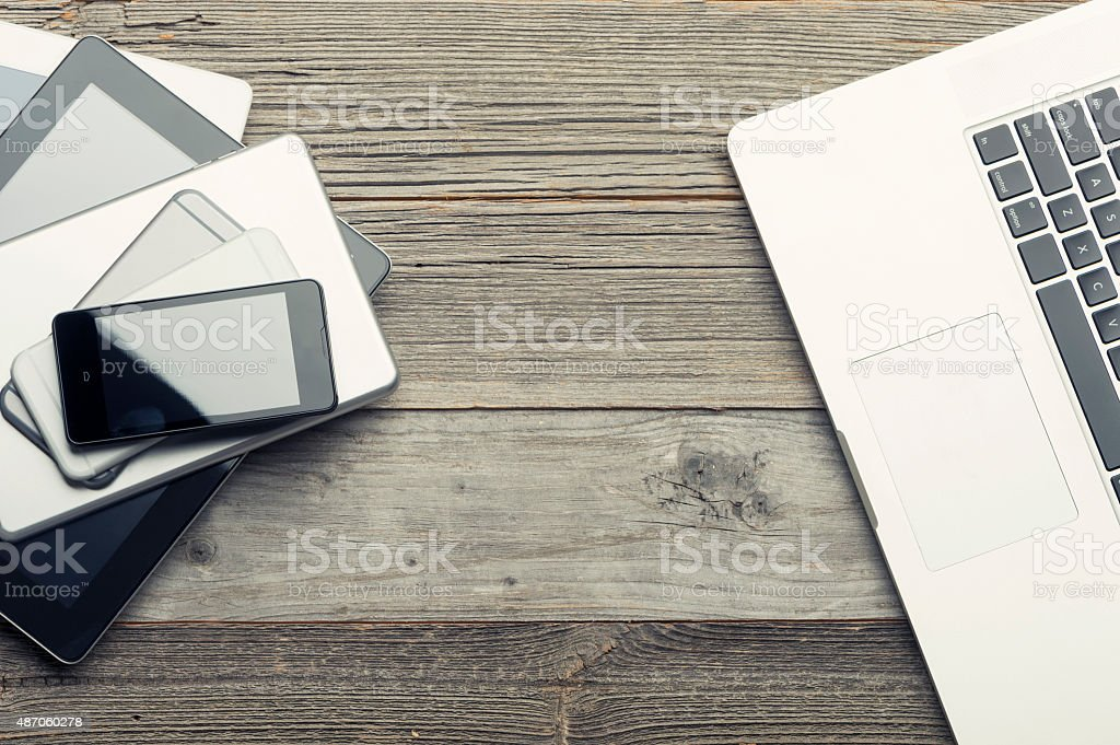 Stack of mobile devices on a wooden table. stock photo