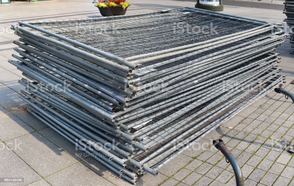 A stack of modular steel fence elements made of galvanized steel grating. Street outdoor sunny autumn day shot royalty-free stock photo