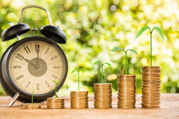 Stapel von Geld Münze angeordnet wie ein Graph auf Holz und Baum Wachstum mit schwarzen Wecker Natur Hintergrund, Konzept der Zeit Geldmengenwachstum Weichzeichnen – Foto
