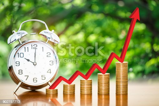 istock Stack of money coins arranged as a graph with red arrow indicates economic upturn and alarm clock on wooden table with blur nature background, concept of time to money growth 902757712