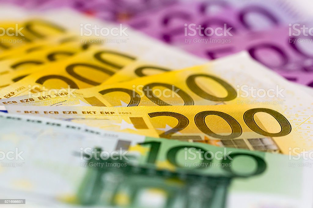 Stack of money with 100 focused 200 and 500 euro Perfect for illustrating e.g. wealth, lottery prizes or banking crises. What is your dream? Aspirations Stock Photo