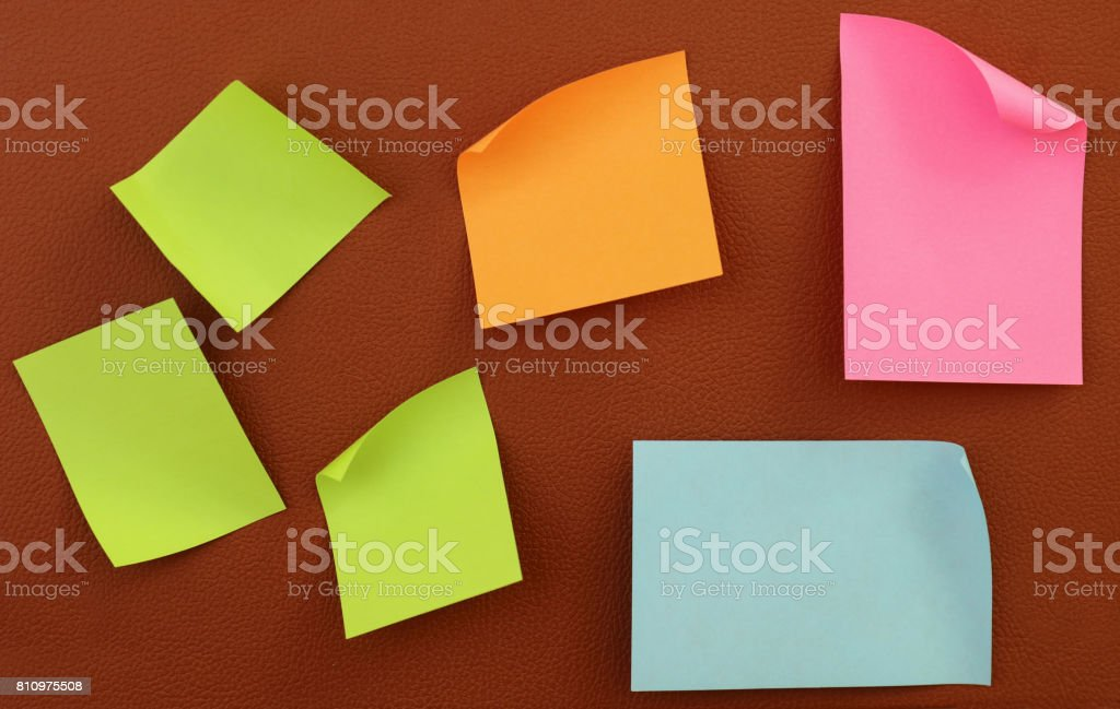Stack Of Multi Colored Adhesive Notes Against Leather Background stock photo