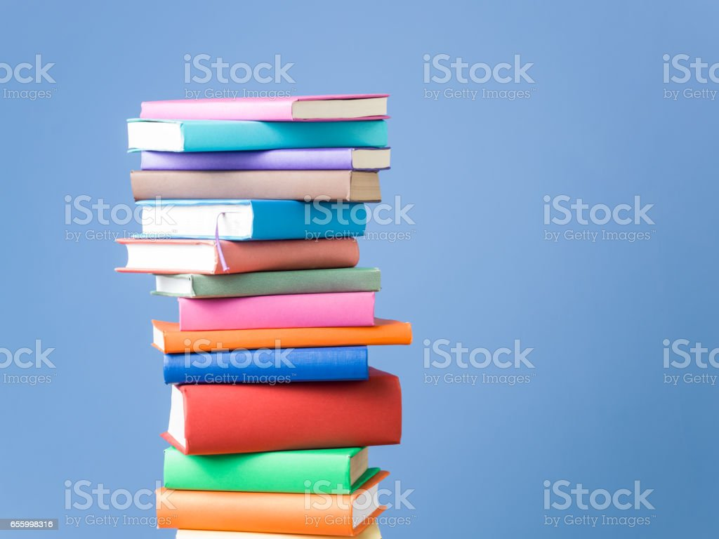 Stack Of Multi Colored Books On Blue Background royalty-free stock photo