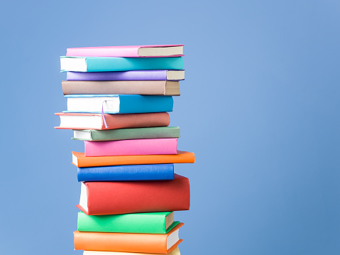 Stack Of Multi Colored Books On Blue Background