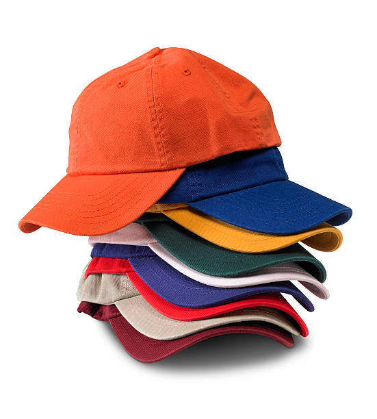 Stack of multi-colored baseball caps isolated on white background stock photo