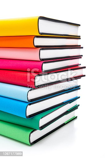 Front view of rainbow colored books arranged in a stack isolated on white background. The composition is at the left of an horizontal frame leaving useful copy space for text and/or logo at the right.High resolution 42Mp studio digital capture taken with SONY A7rII and Zeiss Batis 40mm F2.0 CF lens