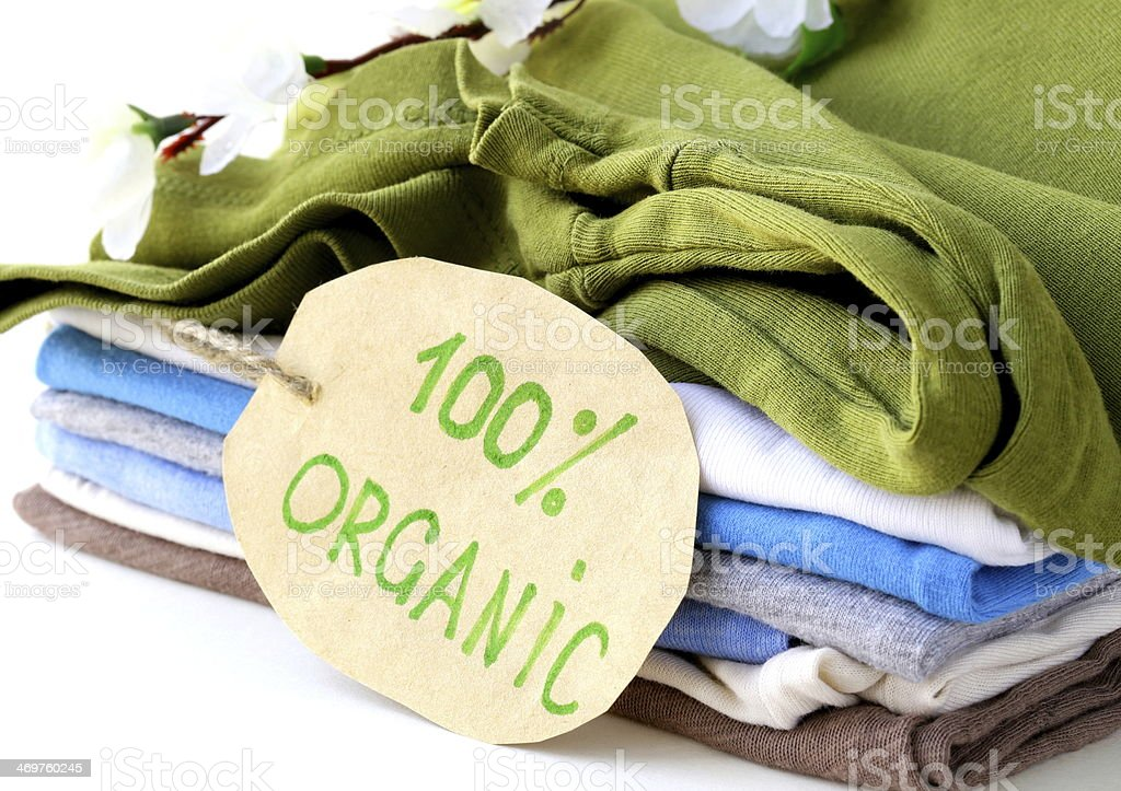 stack of multicolored clothing with 100% organic label stock photo