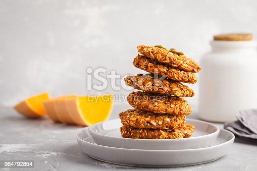 istock Stack of natural oatmeal pumpkin cookies on a gray plate, halloween food, autumn food, vegan food concept. 984792854