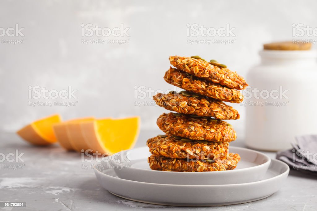 Stack of natural oatmeal pumpkin cookies on a gray plate, halloween food, autumn food, vegan food concept. stock photo