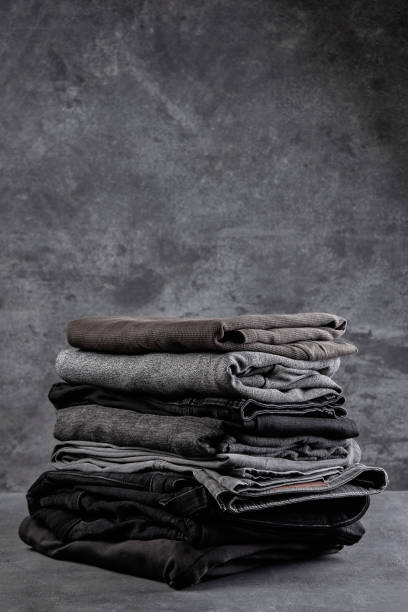 A stack of neatly folded dark clothes isolated on a black gray background close-up