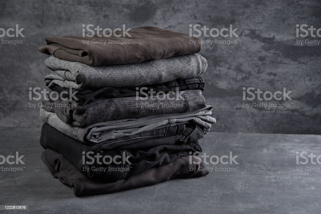 A stack of neatly folded dark clothes isolated on a black gray background close-up A stack of neatly folded dark clothes isolated on a black gray background close-up Autumn Stock Photo