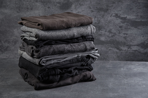 A Stack Of Neatly Folded Dark Clothes Isolated On A Black Gray Background Closeup Stock Photo - Download Image Now