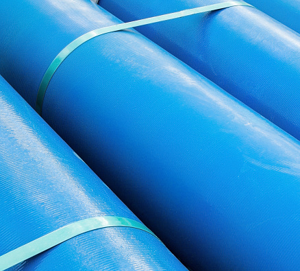 Stack of new blue pipes (tubes). Fluid conveyance. Pipeline construction. Pipes fastened with plastic tape.