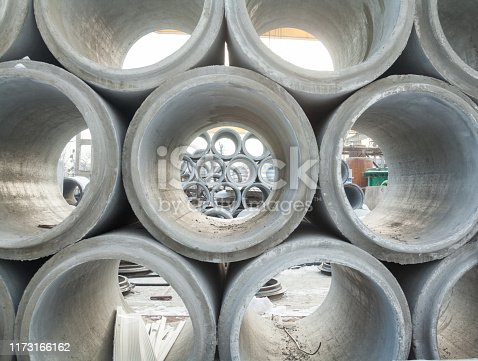 Stack of new concrete pipes. Pipeline construction. Construction material.