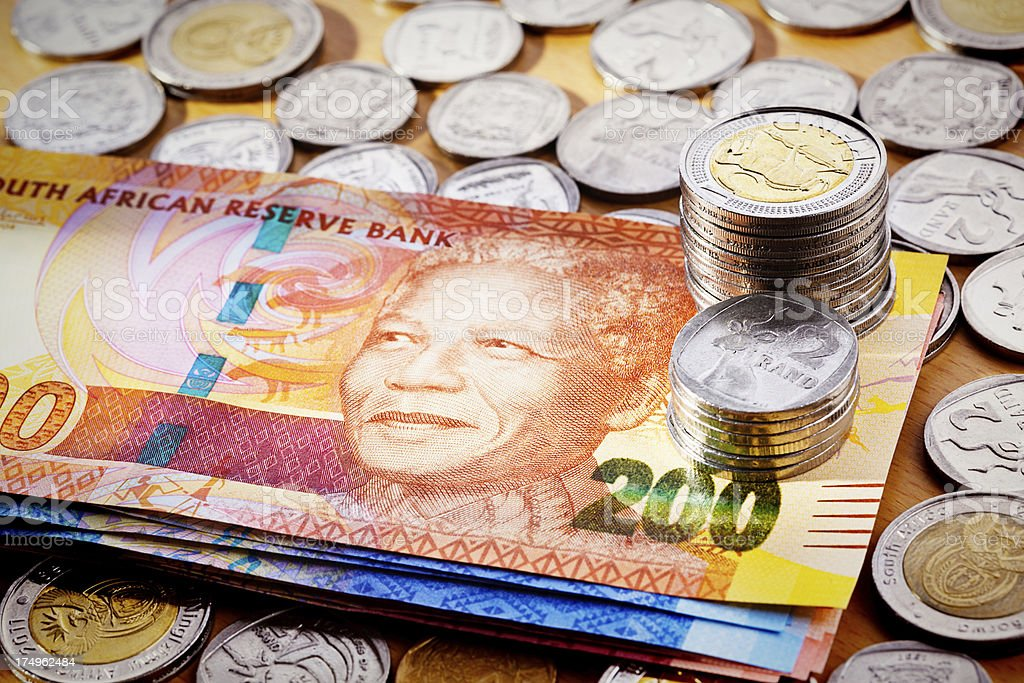 Stack of new South African Mandela banknotes with silver coins stock photo