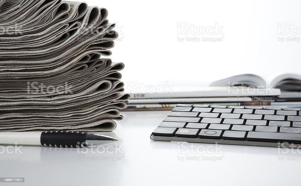 stack of newspapers and keyboard stock photo