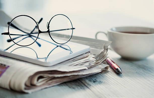 Pila de periódicos, gafas en mesa - foto de stock