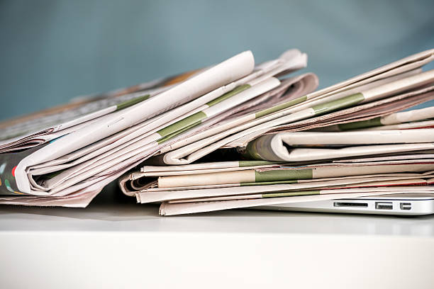 Stack of newspapers, placed on a laptop stock photo