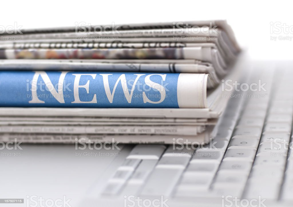 Stack of newspapers resting on laptop keyboard stock photo
