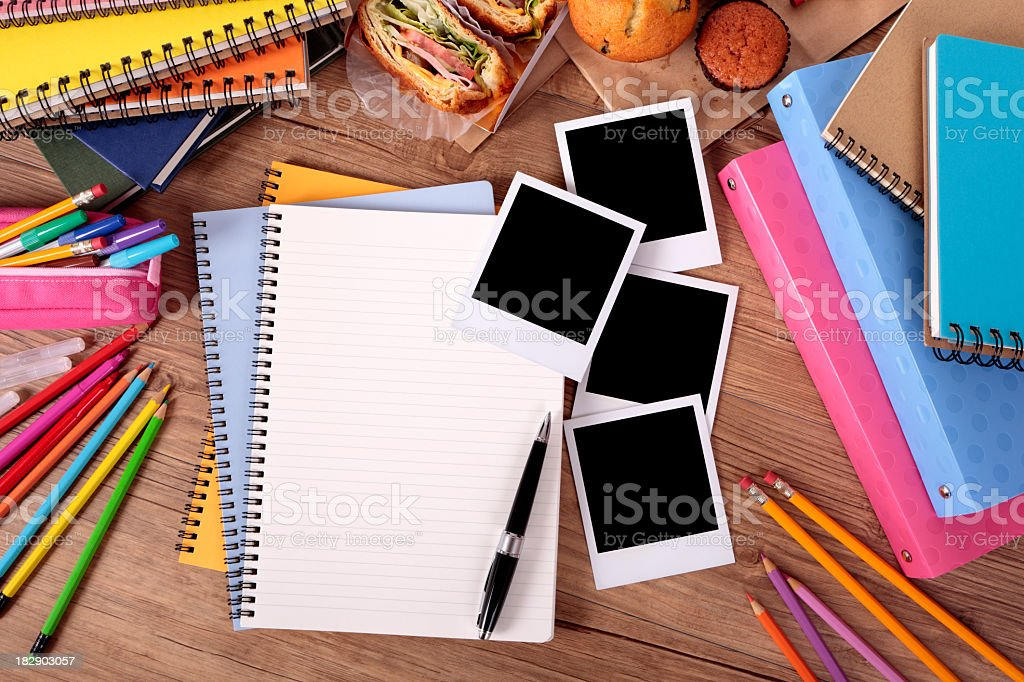 Stack of notepads and pencils with three blank Polaroids stock photo